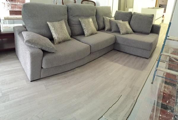 Cheslong tapizada en confortable chenilla gris con cojines a juego tapizados en tela imitación piel de serpiente.