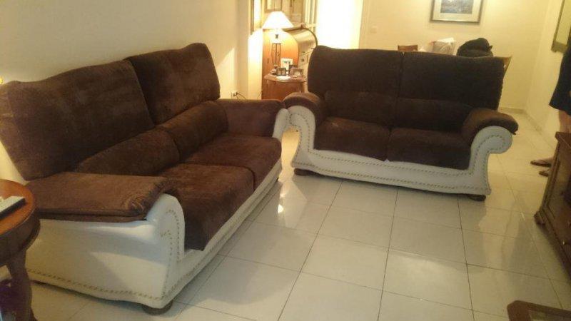 Conjunto de sofás tapizado en chenillas marrón y crudo y cordones en marrón.
