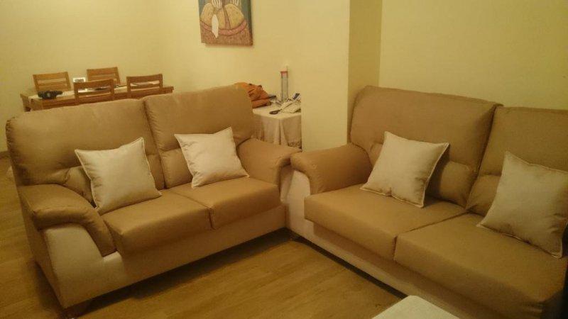 Conjunto de sofás tapizados en telas sintéticas en color caramelo y crema a los que se les ha cambiado las espumas interiores y la de los cojines.