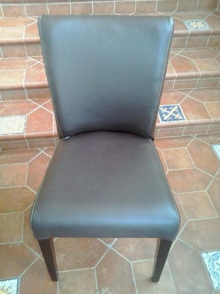 Frontal sillas tapizadas en piel marrón con pespuntes en blanco.