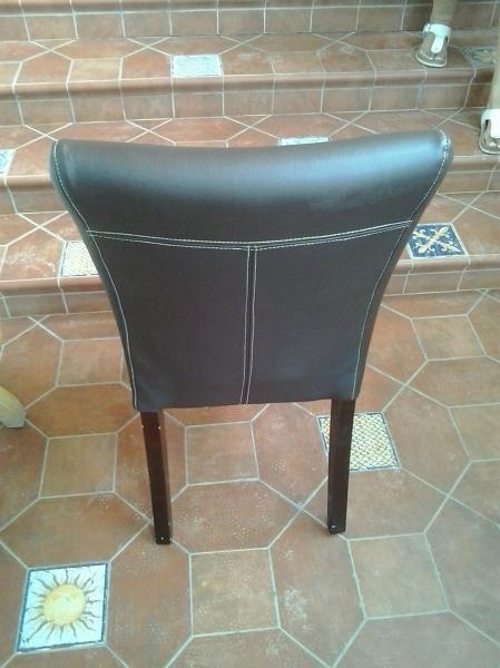 Espaldal sillas tapizadas en piel marrón con pespuntes en blanco.