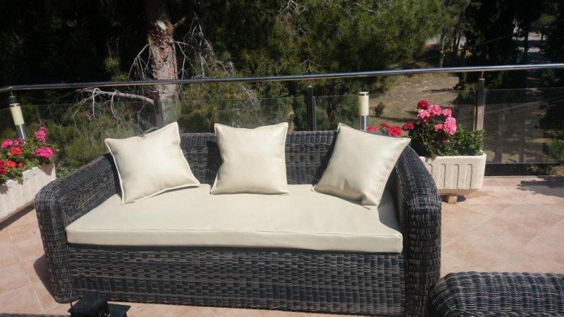 Sofá de mimbre negro al que se le ha puesto una colchoneta de espuma de 30 kg, así como cojines cuadrados, con tapizado en polipiel beige.