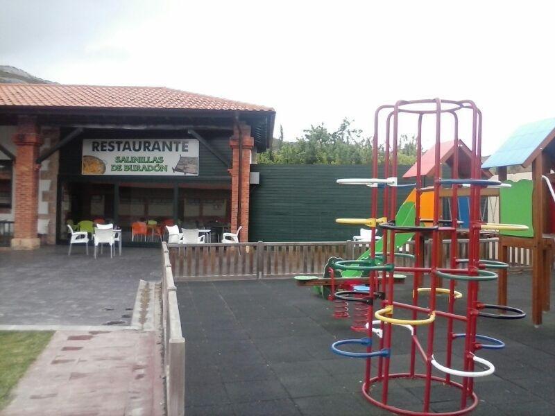 Zona ajardinada exterior con columpios para los niños