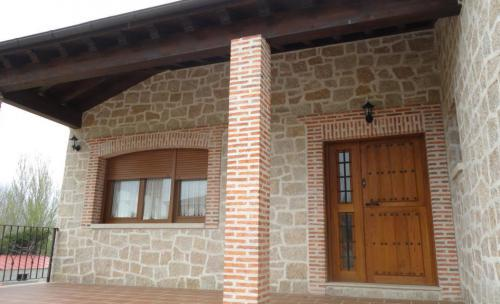 Porche con techo de madera y puerta tambien de madera con cercos y columnas de ladrillo visto.
