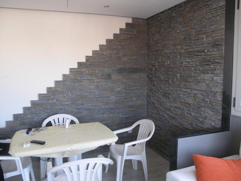 Reforma de vivienda con acabados en piedra en comedor