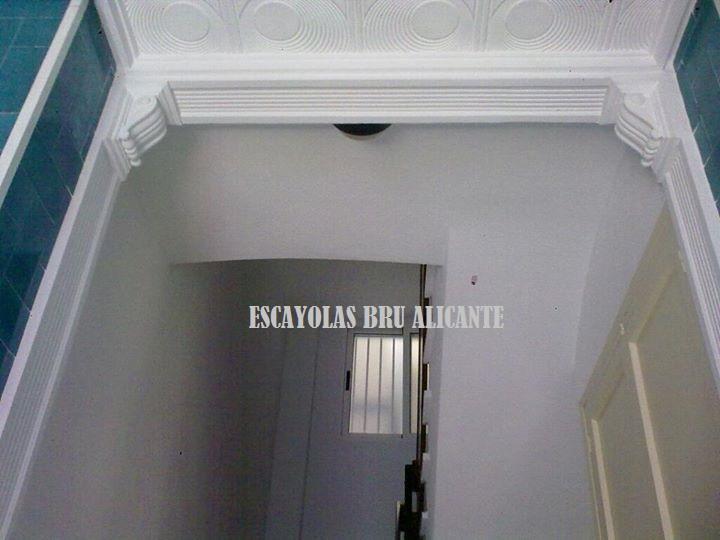 retirar puerta entrada comunitaria e instalación de pilastras y mensulas de escayola, el hall gana en amplitud y luminosidad