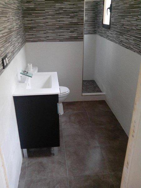 Reforma integral de un cuarto de baño, estilo moderno en blanco y negro, con mampara y plato de ducha de obra.