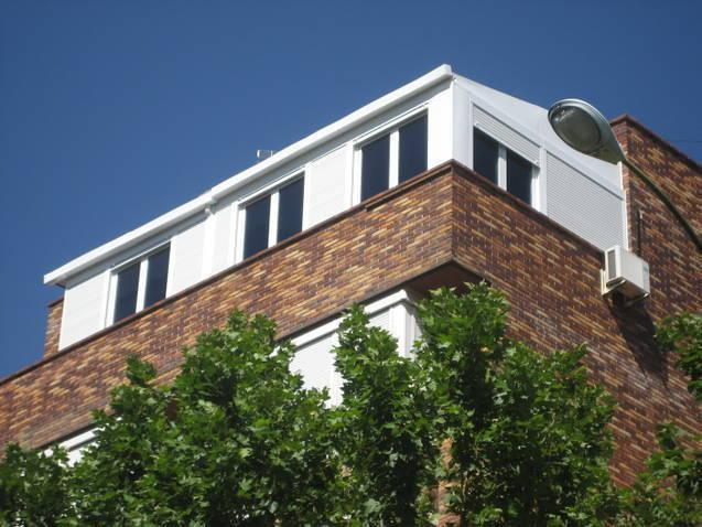 Ático con ventanas oscilobatientes y persianas con panel fijo