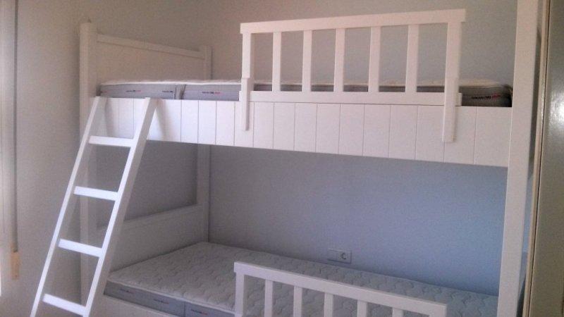 Cama triple lacada en blanco, con escalera y doble barandilla para mayor seguridad, la cama inferior es extraible con ruedas.