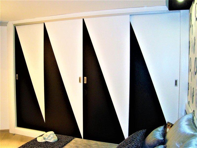 Frente de armario lacado en dos colosres, blanco y negro con una terminación acrílica satinada.También lleva tiradores integrados en la puerta de acero inoxidable