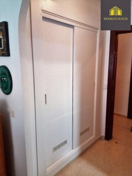 Frente de armario lacado en blanco satinado de puertas correderas con respiradero para mayor ventilación y tirador embutido blanco a juego.