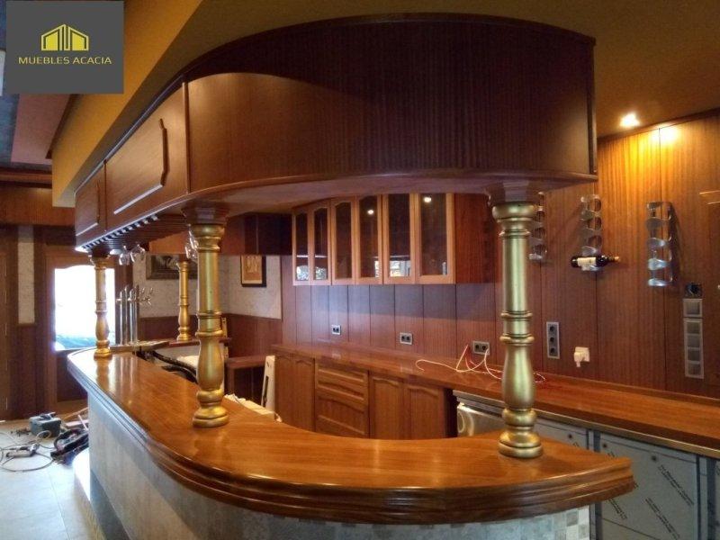 Bar con barra de madera macizo sapelli barnizada con reotán, columnas con terminación oro acrilica, altillos curvos y barra de trabajo independiente con cajones y puertas push.Los enchufes y tomas eléctricas están totalmente integradas en el panelado.