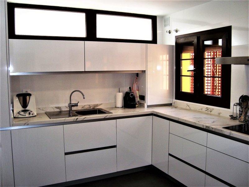 Cocina con encimera dekton, fregadero sobreencimera, calentador oculto y dos muebles abatibles free up con su zócalo de aluminio.