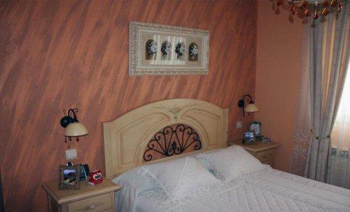 Siroco oblicuo: Decoración en cabecero de habitación de matrimonio con Siroco aplicado en oblicuo y resto de paredes en pintura plástica lisa.