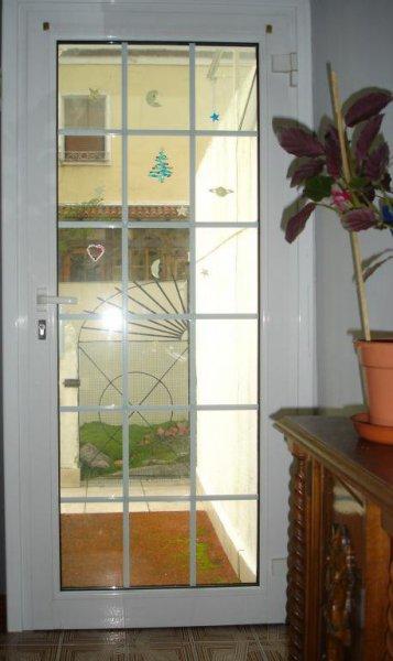 Puerta de salida a terraza. Fabricada con perfiles de aluminio con rotura de puente térmico y cristales con cuarterones.