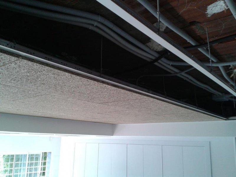 Oficina. Falso techo desmontable de viruta de madera y tabica y faja perimetral de PYL.